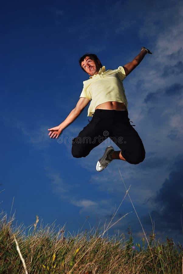 Młody szczęśliwy mężczyzna jest skacze na zielonej łące obraz stock
