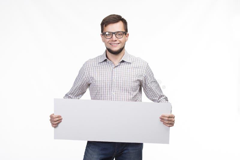 Młody szczęśliwy mężczyzna pokazuje prezentację, wskazuje na plakacie obraz stock