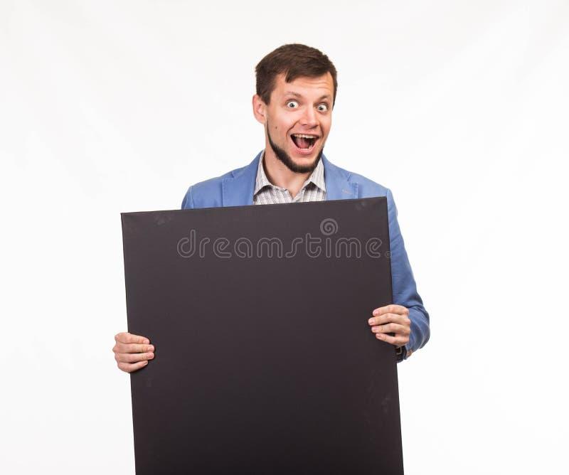Młody szczęśliwy mężczyzna pokazuje prezentację, wskazuje na plakacie obrazy stock