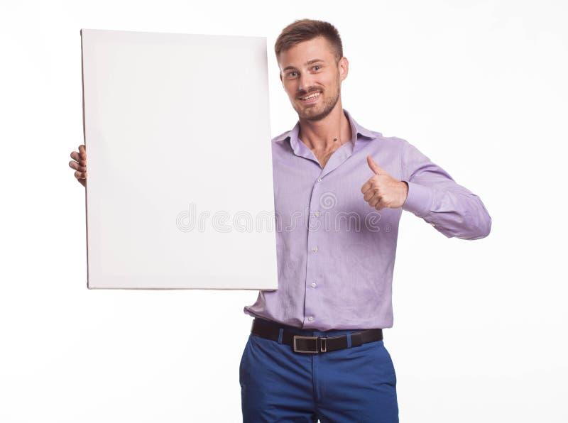 Młody szczęśliwy mężczyzna pokazuje prezentację, wskazuje na plakacie zdjęcie stock