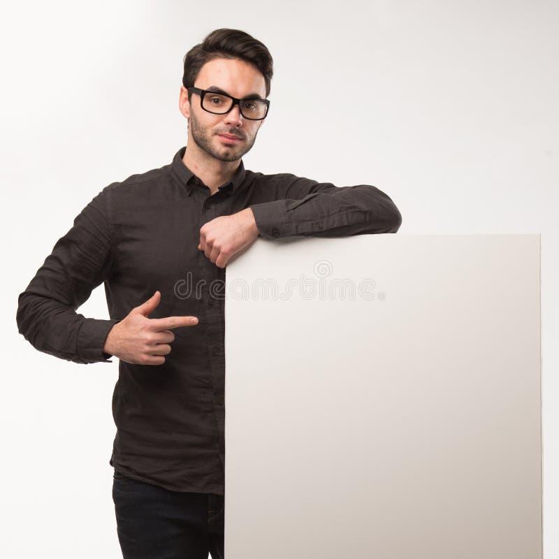 Młody szczęśliwy mężczyzna pokazuje prezentację, wskazuje na plakacie nad szarym tłem fotografia royalty free