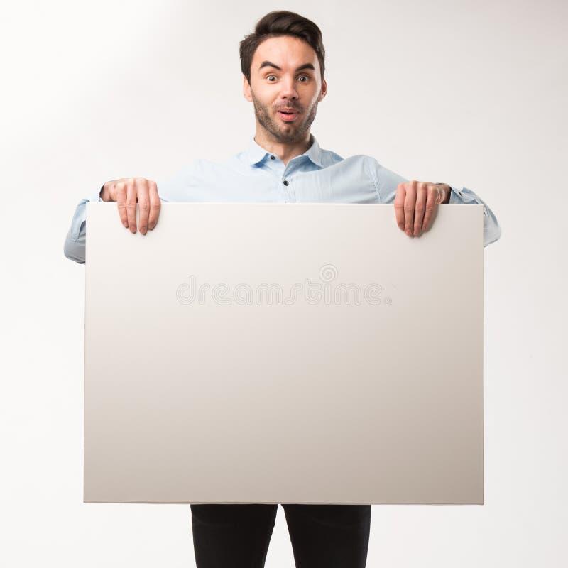 Młody szczęśliwy mężczyzna pokazuje prezentację, wskazuje na plakacie nad szarym tłem obraz stock