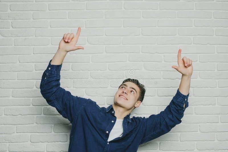 Młody szczęśliwy mężczyzna tryumfuje z nastroszonymi pięściami zdjęcie royalty free