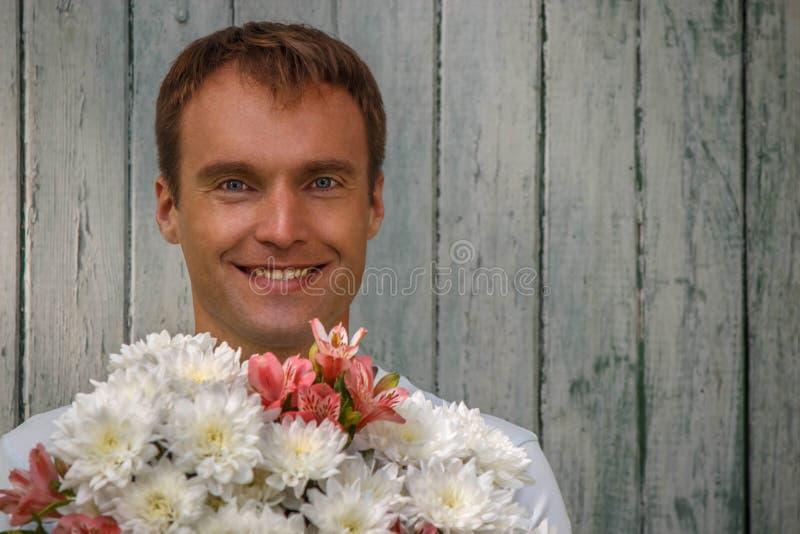Młody szczęśliwy mężczyzna z białymi kwiatami na drewnianym tle zdjęcia royalty free
