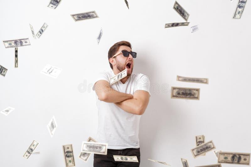 Młody szczęśliwy mężczyzna z brodą w białej koszulowej pozyci pod pieniądze obraz stock