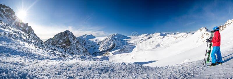 Młody szczęśliwy narciarki obsiadanie na wierzchołku góry i cieszyć się widoku Rhaetian Alps od Presena lodowa, Tonale przepustka fotografia stock