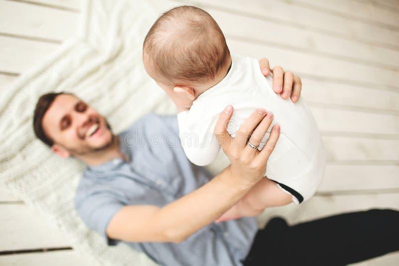 Młody szczęśliwy ojca mienia syn kłama na podłoga w rękach fotografia stock