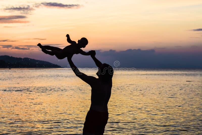 Młody szczęśliwy ojciec trzyma up w jego ręka małym synu stawia on przy plażą w bosej pozyci przed dennymi fala up moczy sa obraz stock