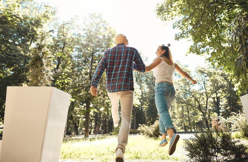 Młody szczęśliwy para bieg przez parka Para w drodze widok z powrotem zdjęcia stock