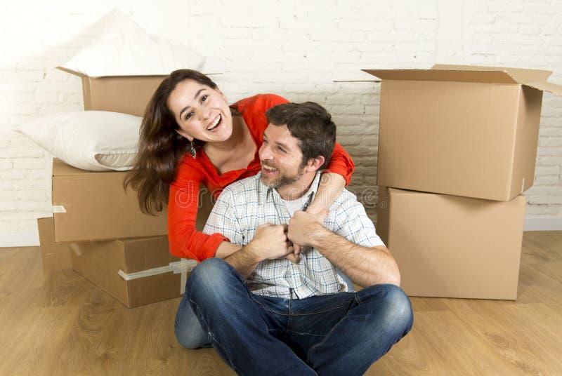 Młody szczęśliwy pary obsiadanie na podłoga wpólnie świętuje ruszać się w nowym mieszkanie domu, mieszkaniu lub zdjęcie stock