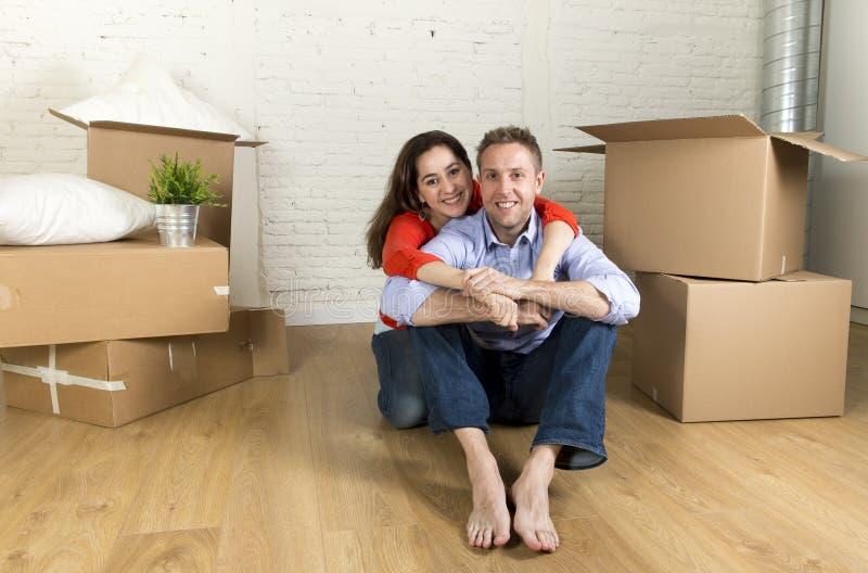 Młody szczęśliwy pary obsiadanie na podłoga wpólnie świętuje ruszać się w nowym mieszkanie domu, mieszkaniu lub fotografia royalty free