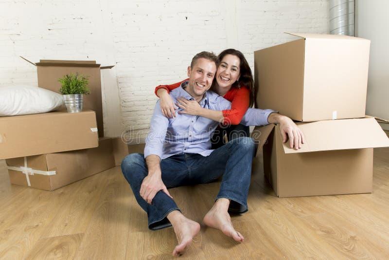 Młody szczęśliwy pary obsiadanie na podłoga wpólnie świętuje ruszać się w nowym mieszkanie domu, mieszkaniu lub obraz stock
