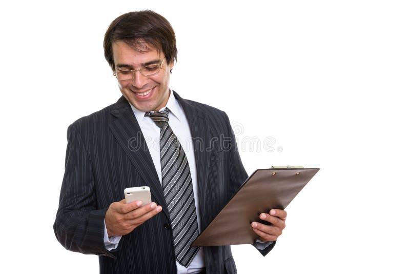 Młody szczęśliwy Perski biznesmen uśmiecha się telefon komórkowego w i używa obraz royalty free