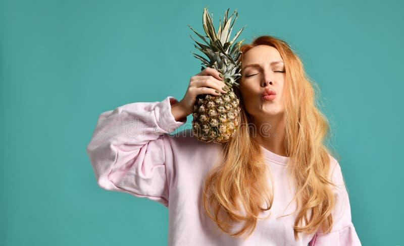 Młody szczęśliwy piękny seksowny kobiety całowanie i mienie ananasa owoc obrazy stock