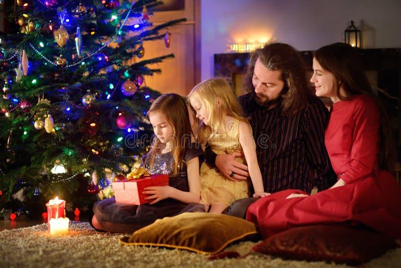 Młody szczęśliwy rodzina składająca się z czterech osób odwija Bożenarodzeniowych prezenty grabą zdjęcia stock