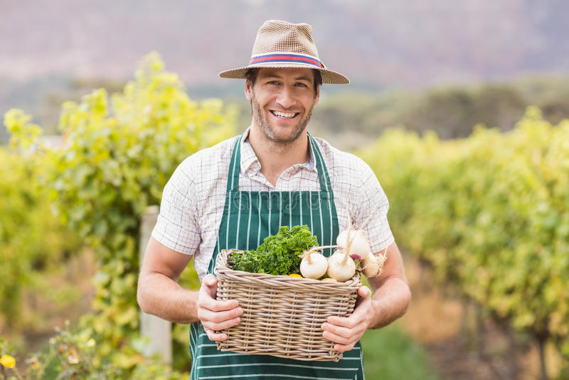 Młody szczęśliwy rolnik trzyma kosz warzywa zdjęcia stock