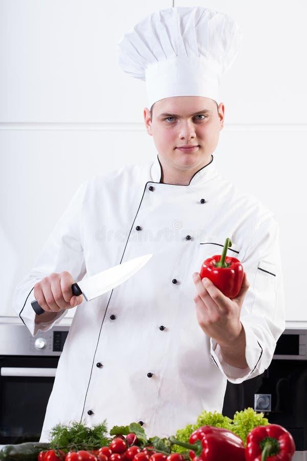 Młody szef kuchni z veggies i nożem zdjęcie royalty free