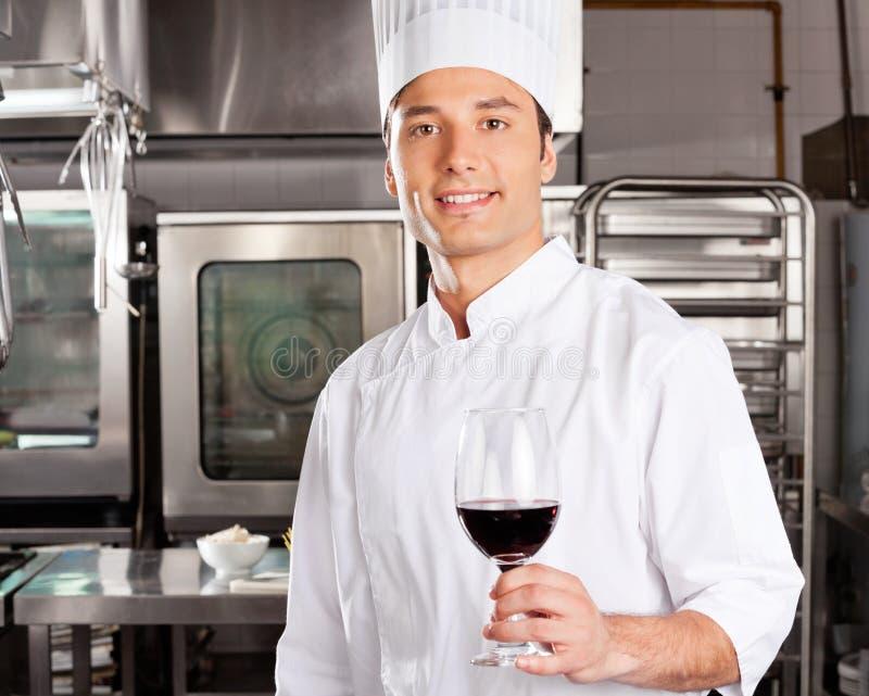 Młody szefa kuchni mienia wina szkło obraz royalty free