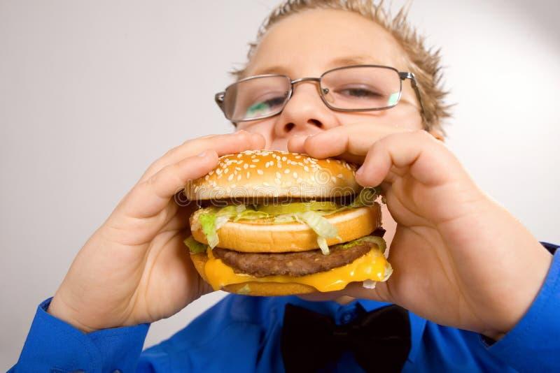 Młody szkolnej chłopiec łasowania hamburger zdjęcia stock