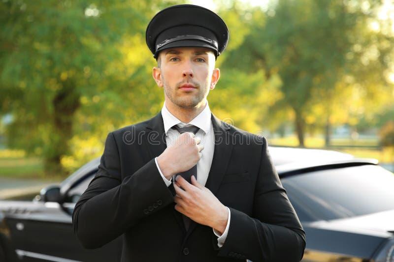 Młody szofer przystosowywa krawat blisko luksusowego samochodu fotografia stock
