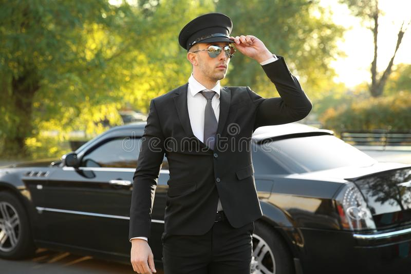 Młody szofer stoi blisko luksusowego samochodu fotografia stock