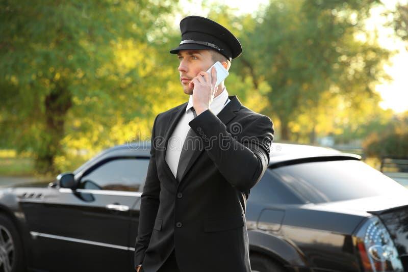 Młody szofera mówienie telefonem komórkowym blisko luksusowego samochodu zdjęcia royalty free