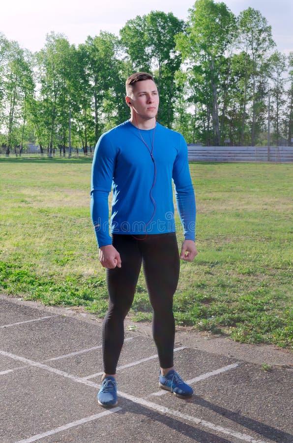 Młody szybkobiegacz przed biegowymi stojakami przy stadium obrazy royalty free