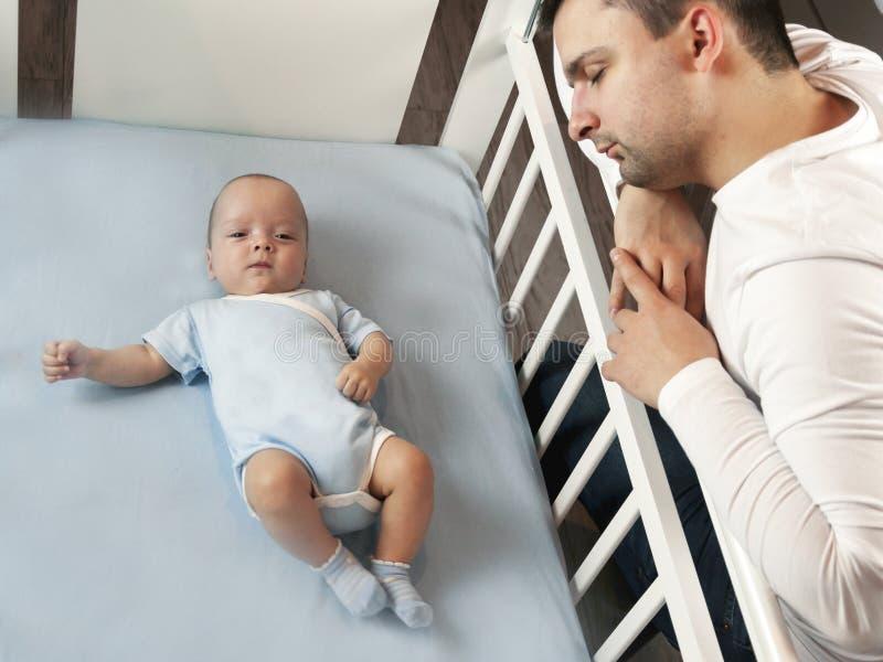Młody tata jest zmęczony stawiać małego dziecka łóżko Taty i syna opieki fatherly pojęcie Selekcyjna ostrość zdjęcia royalty free