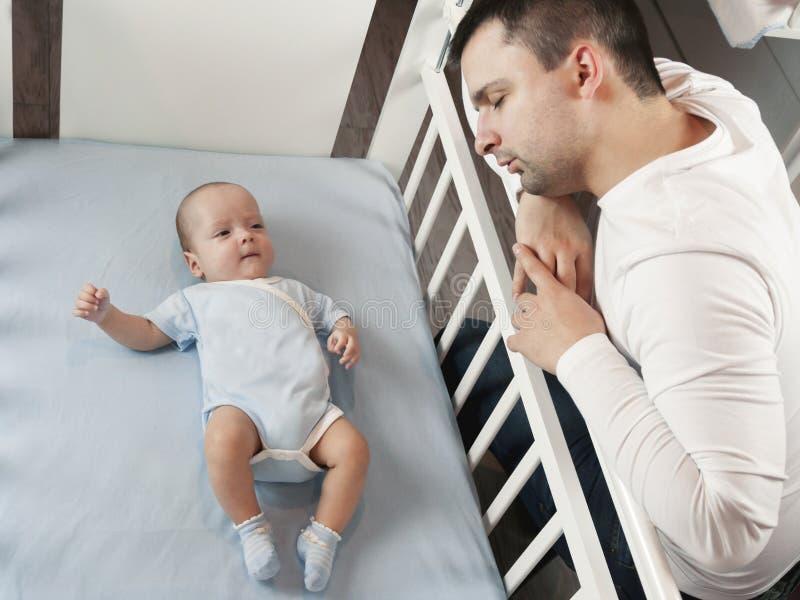 Młody tata jest zmęczony stawiać małego dziecka łóżko Taty i syna opieki fatherly pojęcie Selekcyjna ostrość obrazy stock