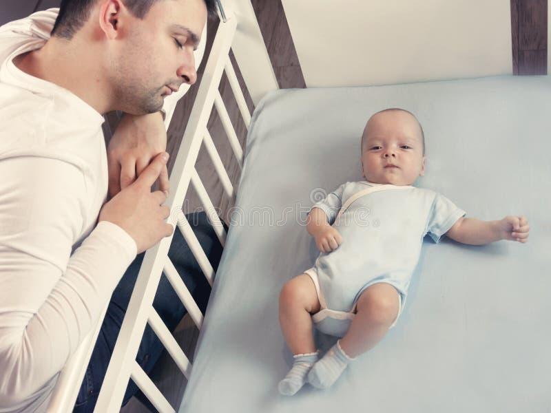 Młody tata jest zmęczony stawiać małego dziecka łóżko Taty i syna opieki fatherly pojęcie Selekcyjna ostrość zdjęcie royalty free