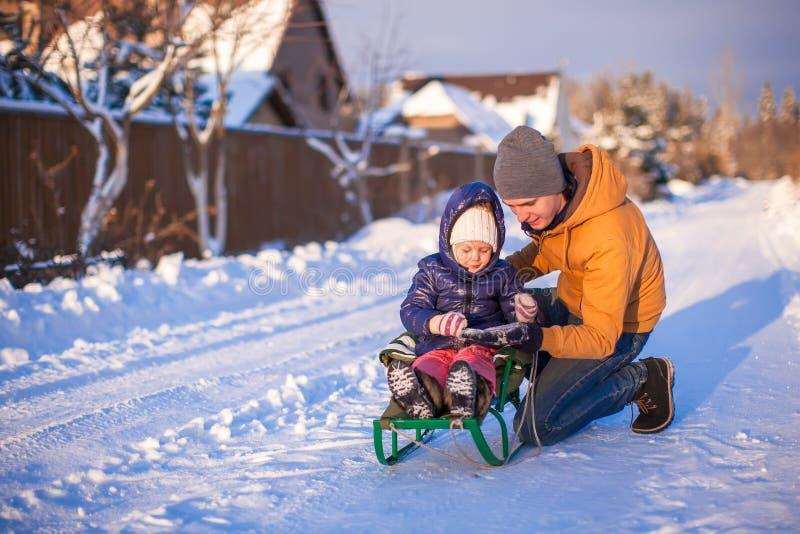Młody tata sledding jego małej uroczej córki dalej zdjęcie royalty free