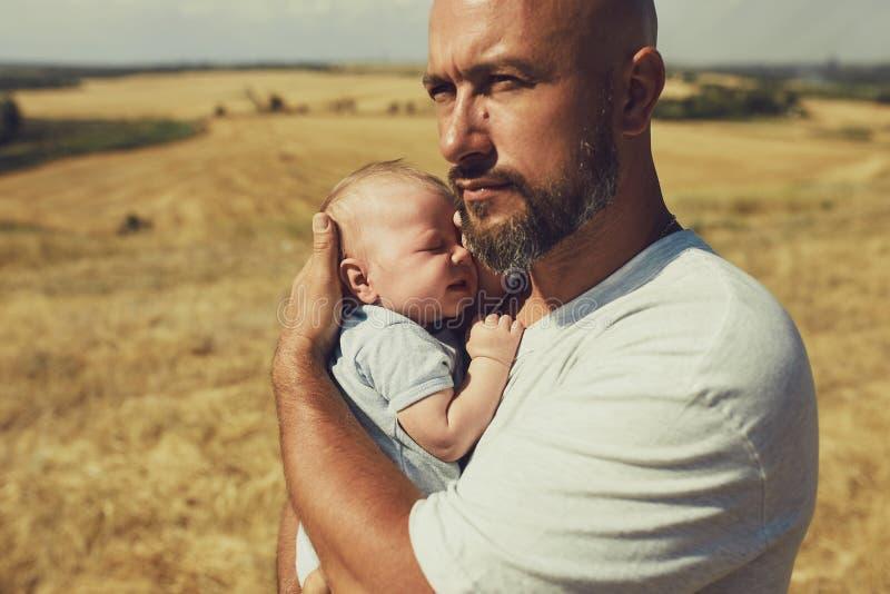 Młody tata trzyma nowonarodzonego dziecka podczas gdy chodzący w naturze szczęśliwy ojciec jest ubranym skróty i koszulkę Mi?dzyn obraz stock