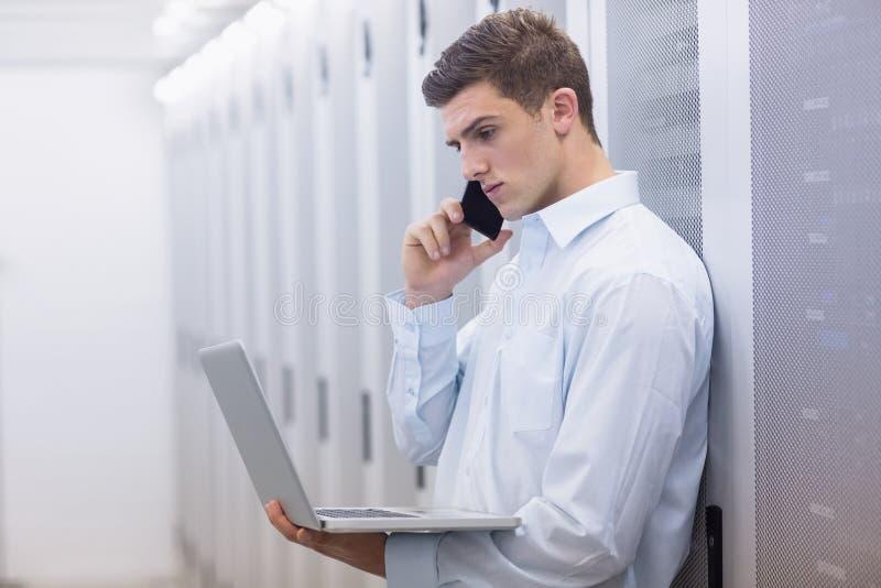 Młody technik dzwoni jego notatnika i używa zdjęcia stock