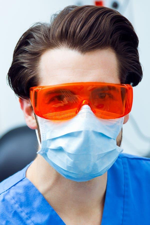 Młody troskliwy dentysta z czerwonymi szkłami zdjęcia stock