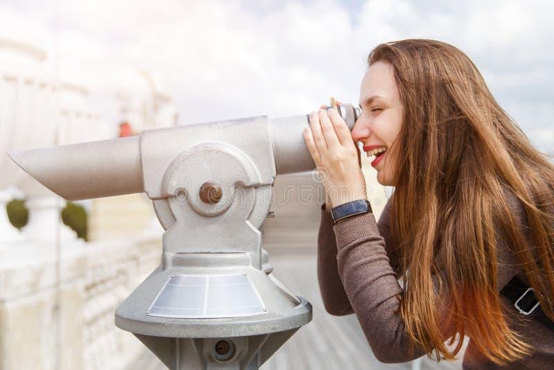 Młody turystyczny dziewczyny dopatrywania miasto przez teleskopu obraz royalty free