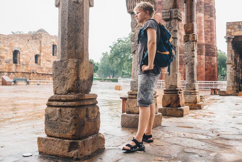 Młody turystyczny mężczyzna czeka gdy intensywna podeszczowa przerwa na jardzie Qu zdjęcie stock