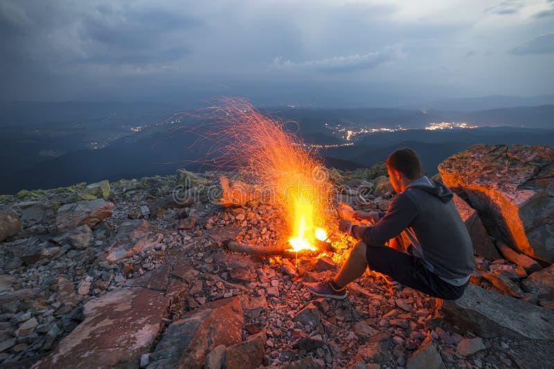 Młody turystyczny mężczyzna obsiadanie na lato nocy przy jaskrawym ogieniem na skale fotografia royalty free