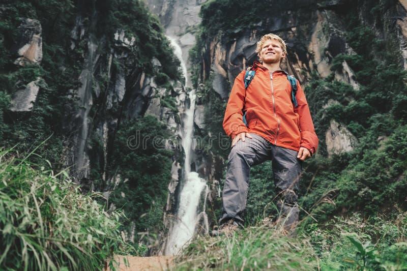 Młody turystyczny mężczyzna pobyt w górze blisko siklawy fotografia stock
