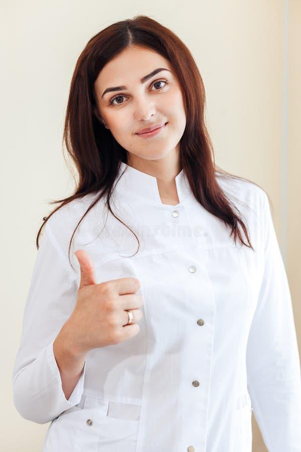 Młody uśmiechnięty żeński brunetki Cosmetologist pokazuje kciuk blisko okno w kosmetologii biurze fotografia stock