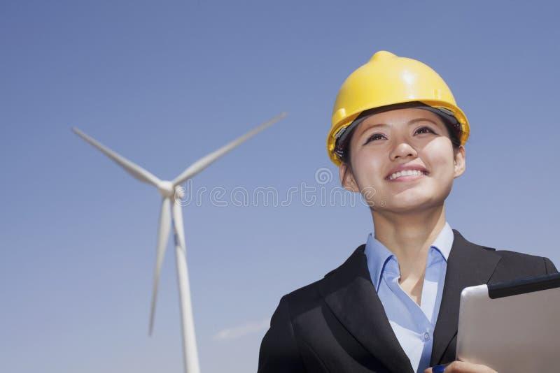 Młody uśmiechnięty żeński inżynier sprawdza silniki wiatrowych na miejscu obrazy royalty free