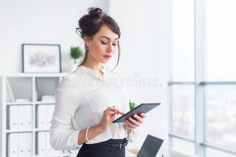 Młody uśmiechnięty żeński urzędnik przy jej miejsca pracy czytaniem, wyszukuje wiadomości reklamy wiadomości używać pastylka komp zdjęcie royalty free