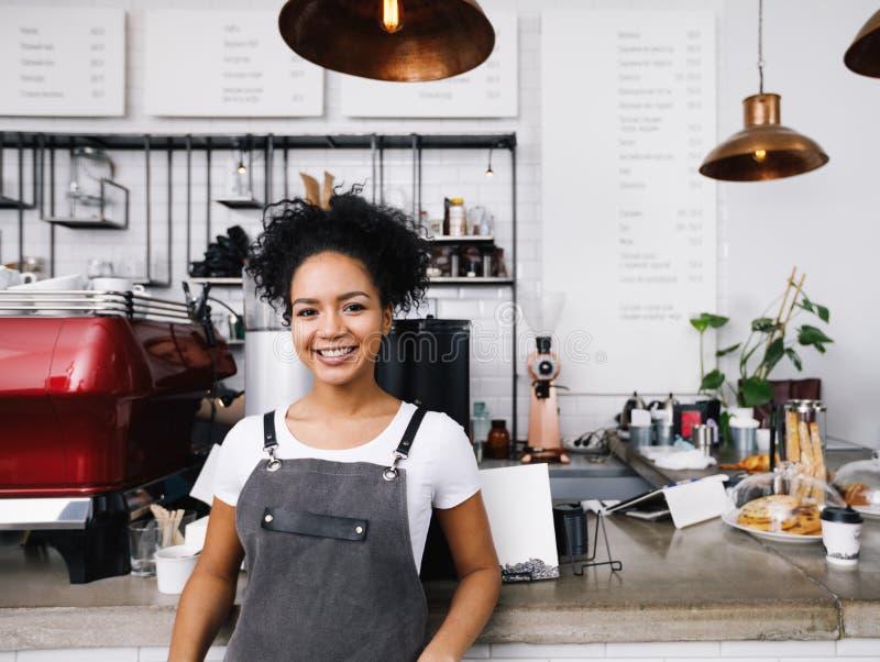 Młody uśmiechnięty barista jest ubranym fartucha zdjęcie royalty free