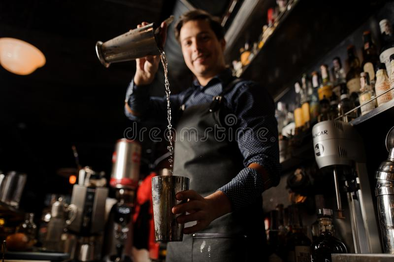 Młody uśmiechnięty barman nalewa alkoholicznego napój od jeden metalu szkła w inny obrazy stock