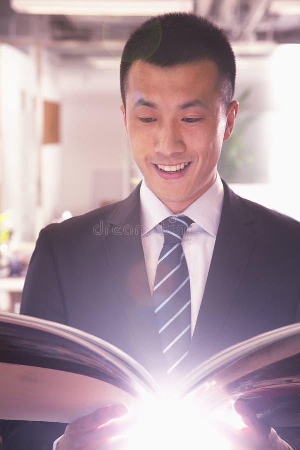 Młody uśmiechnięty biznesmen czyta książkę fotografia stock