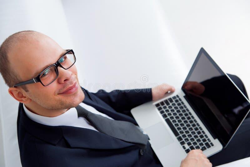 Młody uśmiechnięty biznesmen pracuje z laptopem zdjęcie royalty free