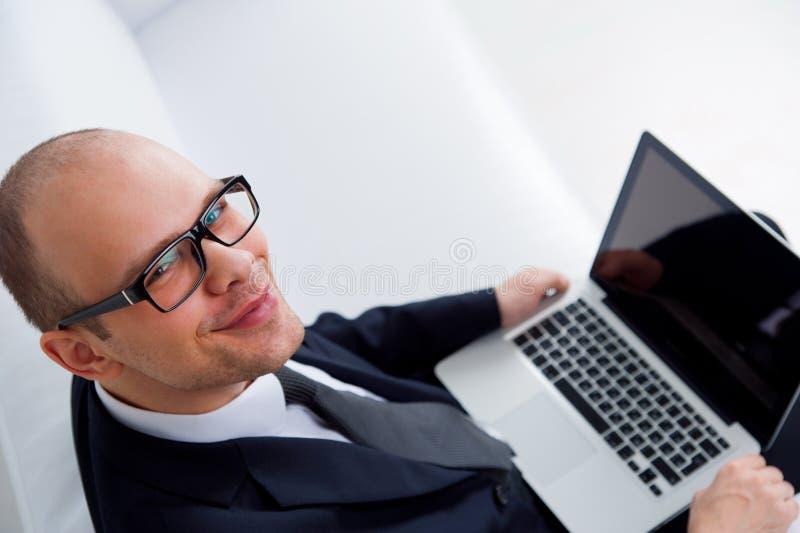 Młody uśmiechnięty biznesmen używa laptop fotografia royalty free