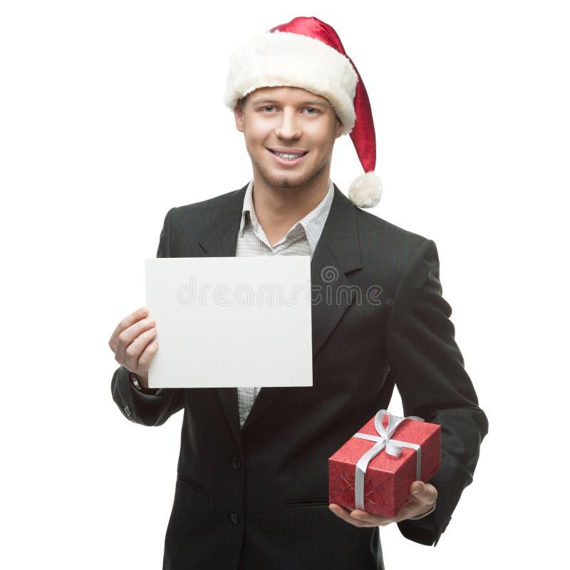Młody uśmiechnięty biznesmen w Santa mienia kapeluszowym znaku fotografia stock