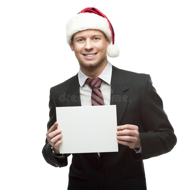 Młody uśmiechnięty biznesmen w Santa mienia kapeluszowym znaku zdjęcie stock