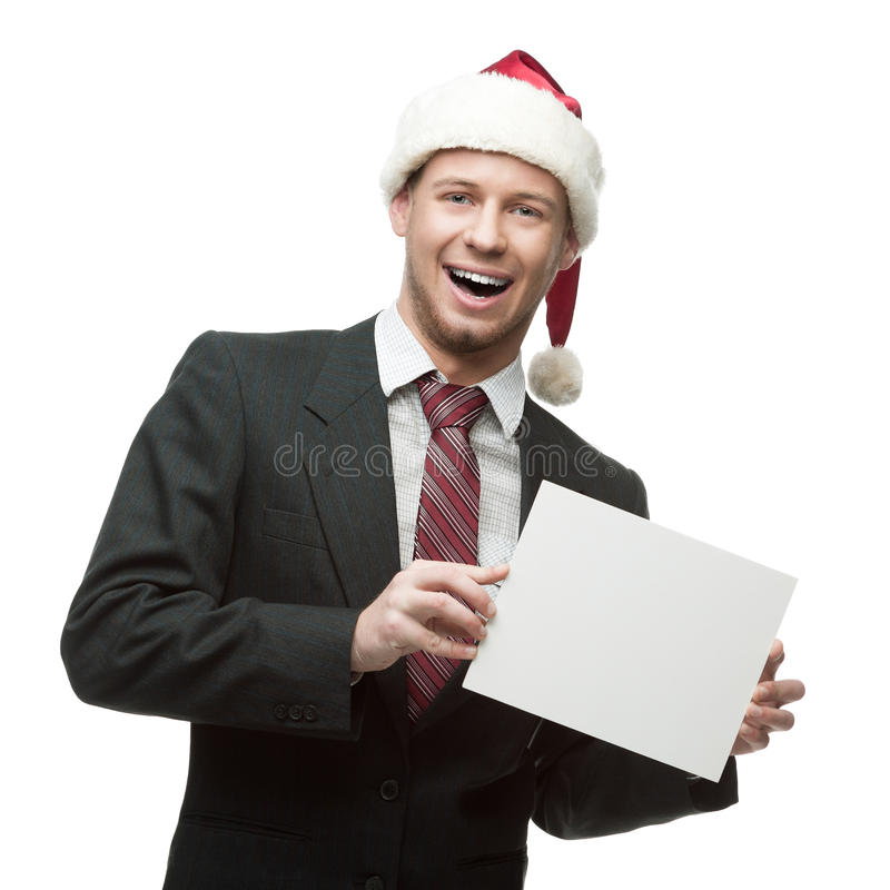Młody uśmiechnięty biznesmen w Santa mienia kapeluszowym znaku obraz royalty free