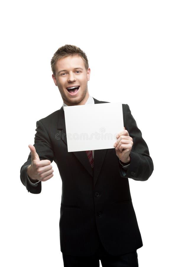Młody uśmiechnięty biznesmena mienia znak fotografia stock